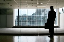 A private investigator with a briefcase waits in an empty office room.